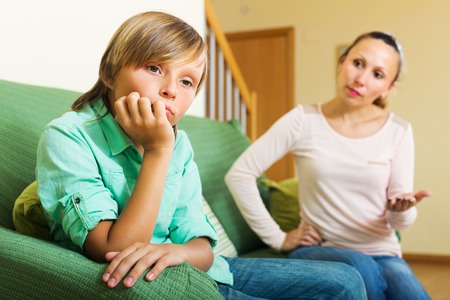 parents: Mother scolding teenager son in living room at home. Focus on boy Stock Photo