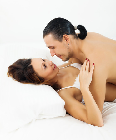 adult sex: adult couple having sex on white sheet Stock Photo