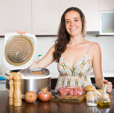 Woman cooking meat with new electric multicooker at home photo