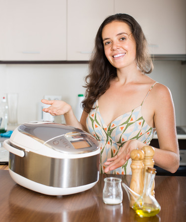 Smiling young housewife cooking with new multicooker in home interior photo