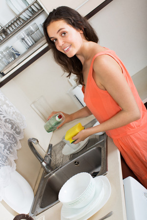 Young smiling woman washing dishes in the kitchen photo