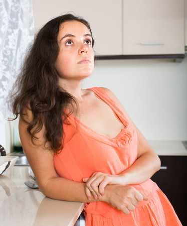 Portrait of sad woman at kitchen at home photo