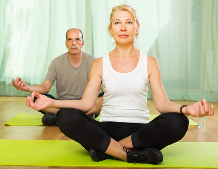Positive elderly couple practicing yoga in the living room at home photo