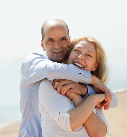 Happy tourist couple at sea beach on holiday smiling and hug Stock Photo