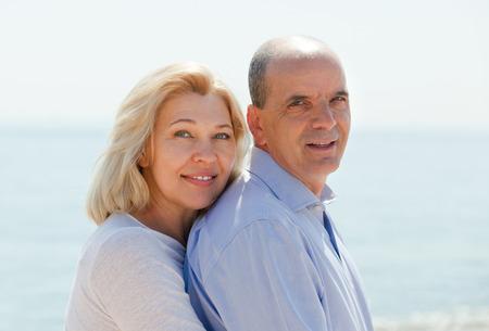 Elderly couple having honeymoon at sea shore in warm season photo