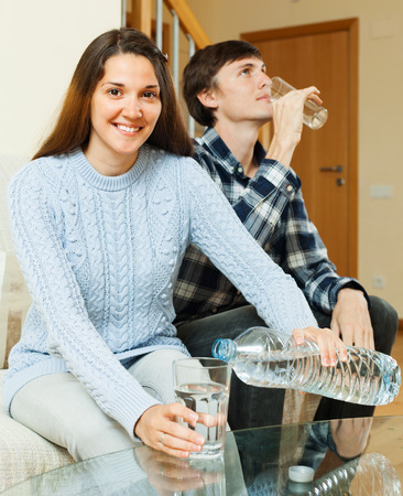 Cherful ordinary couple  drinking water at home photo
