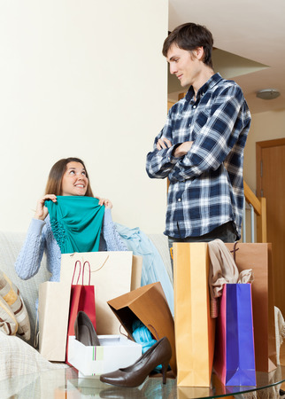 disgruntled: Woman showing purchases  to disgruntled boyfriend in interior