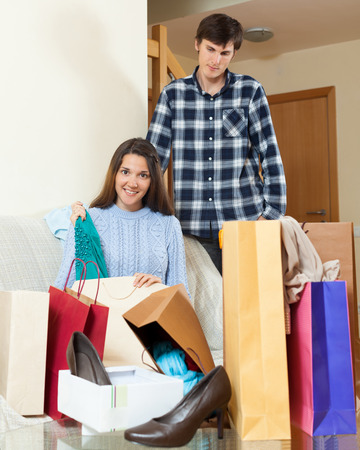 grievance: Smiling woman showing purchases  to disgruntled boyfriend at  home