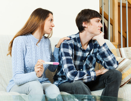 Sad worried woman with pregnancy test with unhappy man at home interior photo