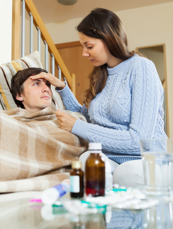 nosotrophy: Woman caring for sick guy who high temperature in home. Focus on man