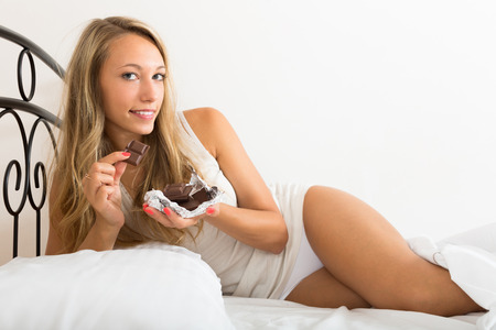 furtively: Smiling young woman lying on bed and eating chocolate