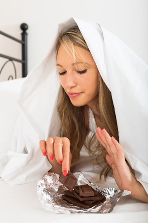 furtively: Woman eating sweet chocolate in her bedroom in the morning