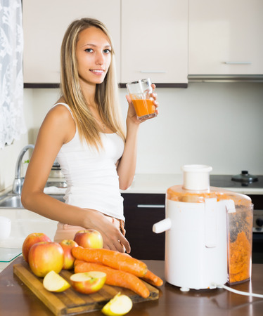 woman with fresh juice in domestic kitchen photo