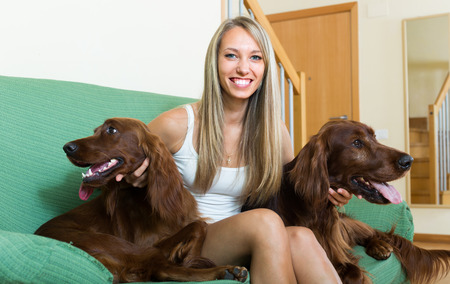hunter playful: Positive smiling girl sitting on sofa with two Irish setters. Focus on girl Stock Photo