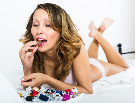 furtively: European woman eating chocolate candy in bed