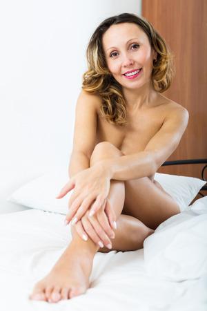 mujer desnuda sentada: Sonriente mujer desnuda sentada en la cama en el dormitorio