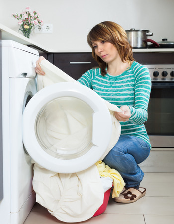 unsound: Home laundry. Unhappy  girl using washing machine at home