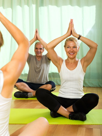 Yoga instructor showing asana to senior attenders photo