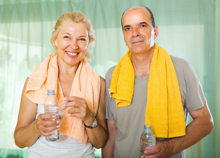 Active elderly spouses with bottles of water  smiling after morning exercises photo