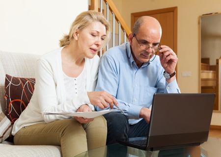 adn: Grave joven hombre adn leer documentos financieros juntos y utilizando equipo port�til en casa interior