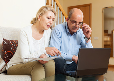 Serious man adn woman reading finance documents together and using laptop in home interior photo