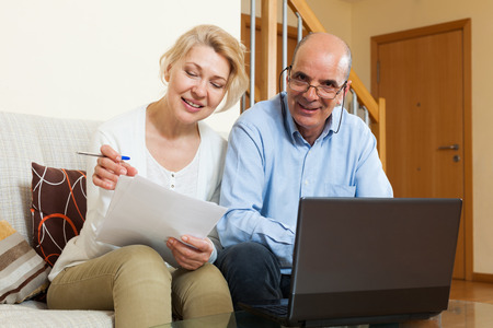 2 people: Mature married couple with financial documents and laptop in home interior Stock Photo