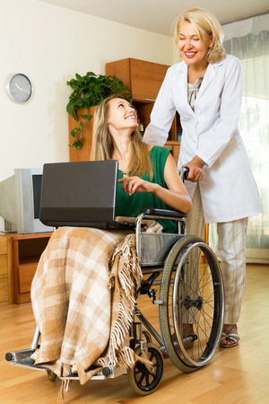 incapacitated: Happy woman in wheelchair working on laptop indoor Stock Photo