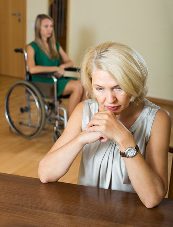 Upset woman and handicapped female having domestic quarrel photo
