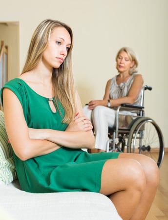 incapacitated: Sad blonde girl and handicapped aged woman having domestic quarrel