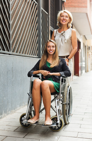 incapacitated: Smiling girl helping handicapped woman