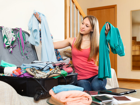 return trip: Happy girl sitting on couch with clothes in hands near the open suitcase Stock Photo