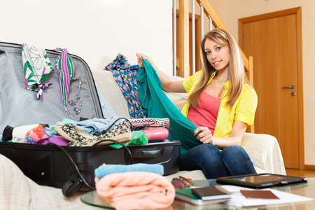 Happy young woman packing a suitcase for travel