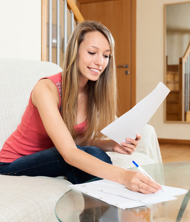 freelancer: Successful female freelancer working with documents on sofa at home Stock Photo