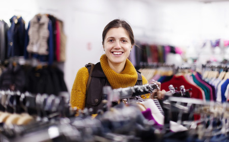 clothing store: Smiling girl choosing  wear at clothing store