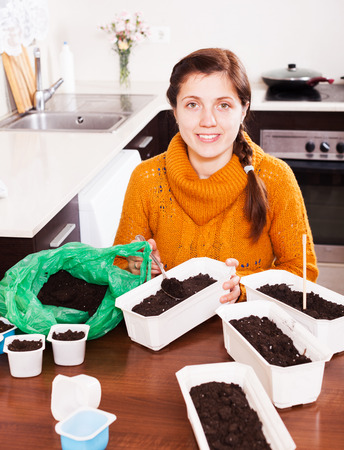 Woman sowing seeds in ground at table in kitchen photo