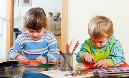 ni�os con l�pices: Dos ni�os jugando con papel y l�pices en el interior de su casa Foto de archivo