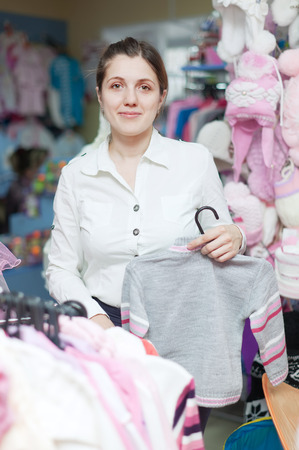 children's wear: Young mother  chooses clothes for daughter at childrens wear store