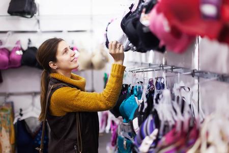 clothing store: Smiling girl choosing  bra at clothing store Stock Photo