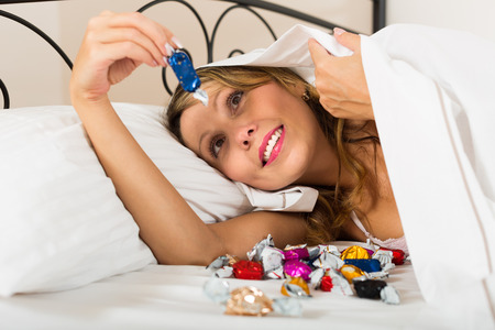 Happy smiling woman laying in bed with sweets in secret
