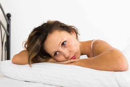 ennui: Upset woman laying in bed with dropped eyes Stock Photo