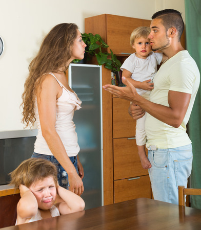 Married couple with two little children having conflict at home photo