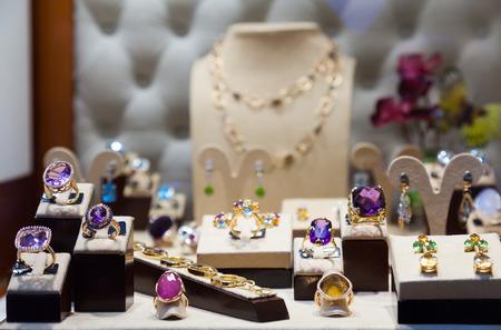 Gouden sieraden met edelstenen in de etalage