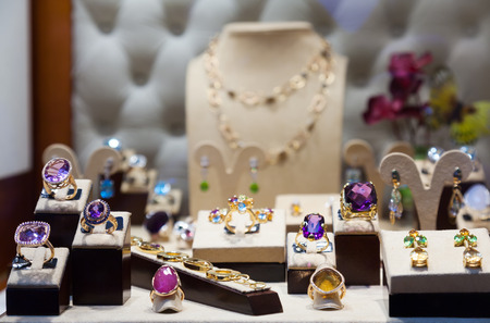 Golden jewelry with gems at showcase Foto de archivo
