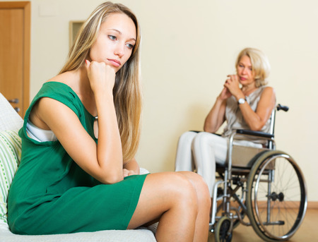 Tired woman and mature disabled person on chair indoor photo