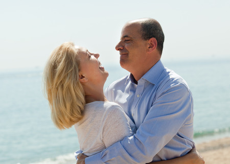 oudoor: Eldelry tourist couple at sea beach on vacation smiling together