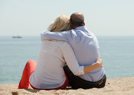 Romantic mature lovers sitting on beach at seashore and enjoying the view photo