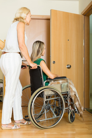 incapacitated: Happy women in wheelchair with assistant at threshold Stock Photo