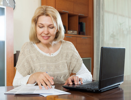 60 something: Serious mature woman staring financial documents with laptop Stock Photo