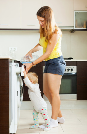 Mother and child using washing machine with laundry detergent photo