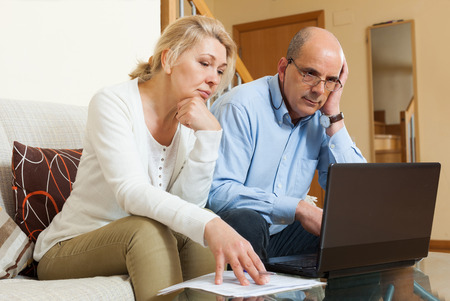 Serious mature couple  with laptop  at table in home Stock Photo